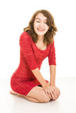 Pretty teenage girl with braces in red dress sitting. A pretty teenage brunette girl with braces on her teeth, with eyes closed, sitting on a white surface with Royalty Free Stock Image