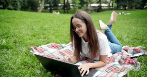 Woman lying on lawn with laptop stock video footage