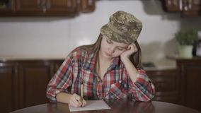 Pretty teenage girl in checkered shirt and military hat of her father on the head writing a letter sitting at home at stock video