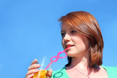 Pretty Teenage girl drinking through a straw Stock Photography