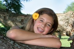 Pretty teenage girl with flower in her hair. Pretty teenage girl resting on a tree branch smiling with a flower in her hair Royalty Free Stock Image