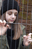 Pretty teenage girl gripping a wire fence Stock Photo