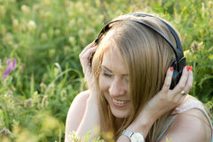 Pretty teenage girl with headphones on the grass. One of the photos Made during a photo shoot of Russian girl in summer at sunset Royalty Free Stock Image