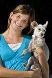 Pretty teenage girl holding her dog. A pretty teenage girl holds her pet dog royalty free stock photos
