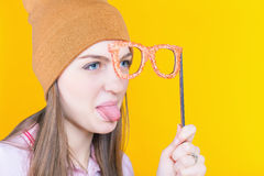 Pretty teenage girl holding masquerade glasses for party. Funny teenage girl holding masquerade glasses for party. Fashion student. Show tongue. Envy Stock Photo