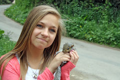 Pretty teenage girl holding on to a squirrel Royalty Free Stock Photo
