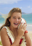 Pretty teenage girl listening to a seashell Royalty Free Stock Photo
