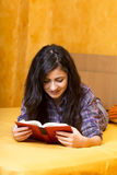 Pretty teenage girl lying in bed and reading a  book Stock Images