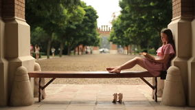 Pretty teenage girl lying down on bench in university campus and reading a book barefoot.  stock video