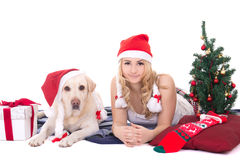 Pretty teenage girl in pajamas lying with dog in santa hat isola Stock Photography