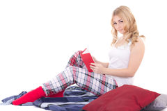 Pretty teenage girl in pajamas sitting with book isolated on whi Stock Image