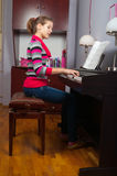 Pretty teenage girl playing on piano Stock Photos