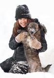 Pretty teenage girl plays with her dog. In thick snow stock images