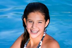 Pretty teenage girl in a pool. Pretty teenage girl smiling in a swimming pool wet hair Stock Photos