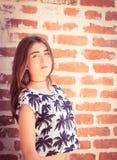 Pretty teenage girl posing next to a  brick wall Royalty Free Stock Image