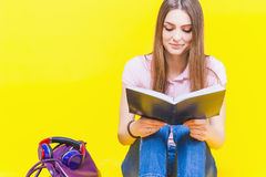 Pretty teenage girl reading a book. Fashion student. Bag. Color Royalty Free Stock Photo