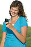 Pretty teenage girl reading text message. A pretty teenage girl smiles while reading a text message stock photos