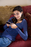 Pretty teenage girl relaxing at sofa texting Royalty Free Stock Images