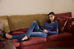 Pretty teenage girl relaxing at sofa texting Stock Photos