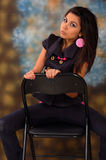 Pretty teenage girl seated on a chair Stock Images
