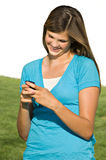 Pretty teenage girl sending text message. A pretty teenage girl smiles while sending a text message stock image