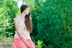 Pretty teenage girl sitting against green leaves Royalty Free Stock Images