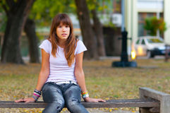 Pretty teenage girl sitting on the bench Stock Images