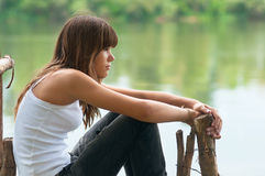 Pretty teenage girl sitting on the dock Royalty Free Stock Photography