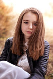 Pretty teenage girl sitting outdoors Stock Photos
