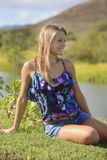 Pretty teenage girl sitting by a river Royalty Free Stock Photos