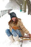 Pretty teenage girl sitting on the sledges Royalty Free Stock Photography