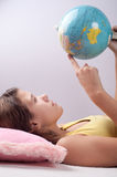 Pretty teenage girl studies earths globe Stock Photos