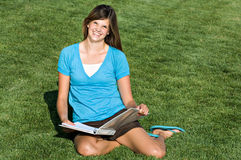 Pretty teenage girl studying in the grass. A pretty teenage girl studies in a grassy field royalty free stock images