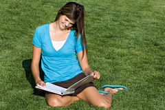 Pretty teenage girl studying in the grass. A pretty teenage girl studies in a grassy field stock images