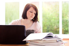 Pretty teenage girl studying at home Royalty Free Stock Image