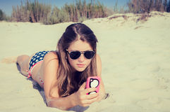 Pretty teenage girl in sunglasses on the beach Stock Image
