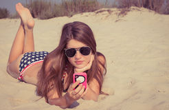 Pretty teenage girl in sunglasses lying on the beach Royalty Free Stock Image