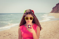 Pretty teenage girl in sunglasses and  in a pink dress on the be Royalty Free Stock Images