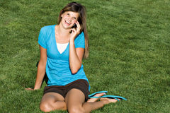 Pretty teenage girl talk on cell phone. A pretty teenage girl talks on her cell phone while seated in a grassy field royalty free stock image