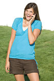 Pretty teenage girl talking on cell phone. A pretty teenage girl laughs while talking on her cell phone royalty free stock images