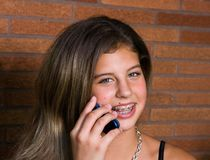 Pretty teenage girl talking on the phone. Pretty teenage girl with braces talking on a cell phone outside on a porch royalty free stock photography