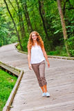 Pretty Teenage Girl Walking in a Park Stock Images