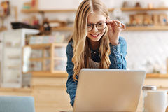 Pretty teenage girl working on laptop and adjusting glasses. Interesting task. Charming fairy-haired girl working in the coffee bar and typing something on the Stock Photography