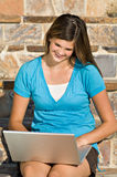 Pretty teenage girl working on laptop computer. A pretty teenage girl smiles as she works on her laptop computer royalty free stock photos