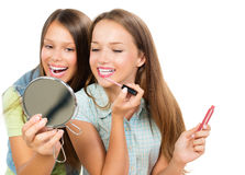 Pretty Teenage Girls. Applying Make up and Looking in the Mirror Stock Images