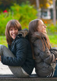 Pretty teenage girls laughing and joking in park. Pretty teenage girls laughing and joking while sitting in the park on beautiful autumn day Stock Photos