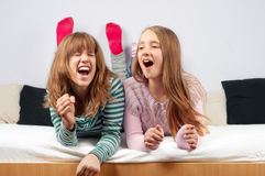 Pretty teenage girls singing. While lying in bed Stock Photography