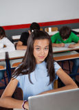 Pretty Teenage Schoolgirl Sitting With Laptop In Royalty Free Stock Photography