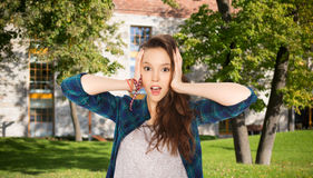 Pretty teenage student girl holding to head Royalty Free Stock Image