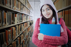 Pretty teenage student standing in library Stock Photography